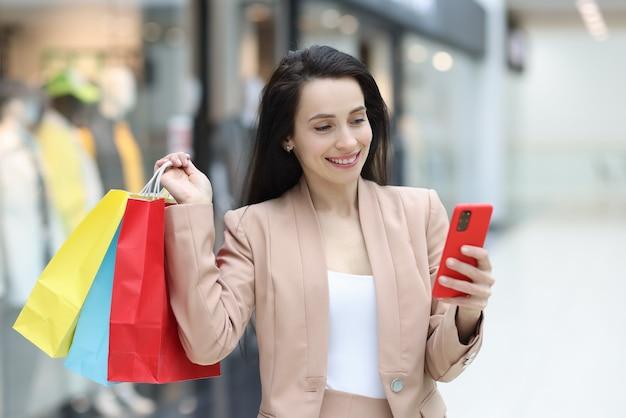 笑顔の女性がスマホを手に持ってモールで購入