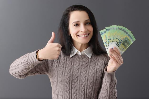 笑顔の女性は親指を立て、100ユーロ紙幣の迅速な収益と投資の概念