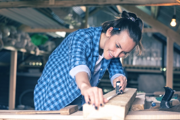 Smiling woman in a home workshop measuring tape measure a wooden board before sawing, carpentry