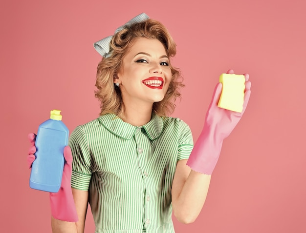 Smiling woman housewife dressed in retro style. happy housekeeper. retro woman cleaner. pinup woman hold soup bottle, duster. cleanup, cleaning services, wife.