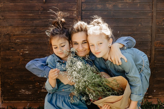 Smiling woman hugging daughters with bouquet