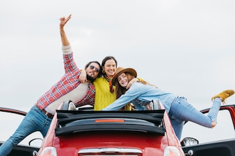 Smiling woman hugging happy man and cheerful lady and leaning out from car
