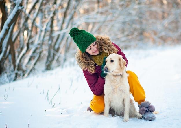Улыбающаяся женщина обнимает свою собаку золотистый ретривер