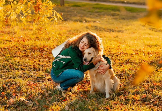 Smiling woman hugging her pet golden retriever dog near face
