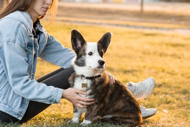 彼女のペットのウェルシュコーギー犬を顔の近くで抱き締める笑顔の女性。秋の日屋外を歩く女性と遊ぶウェルシュコーギー犬。ペットの愛と世話。