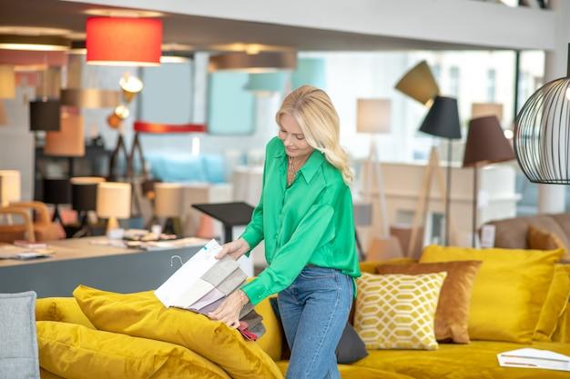소파 근처에 서 고 그녀의 손에 직물 샘플을 들고 녹색 셔츠에 웃는 여자.
