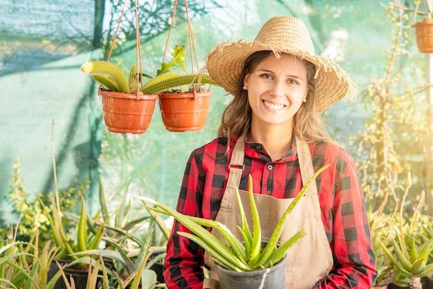 彼女の手にアロエ植物を持つ植物保育園で笑顔の女性緑の趣味