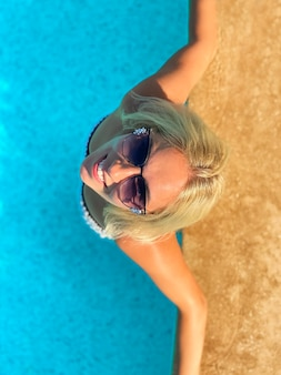Улыбающаяся женщина в бассейне. летняя концепция. вид сверху