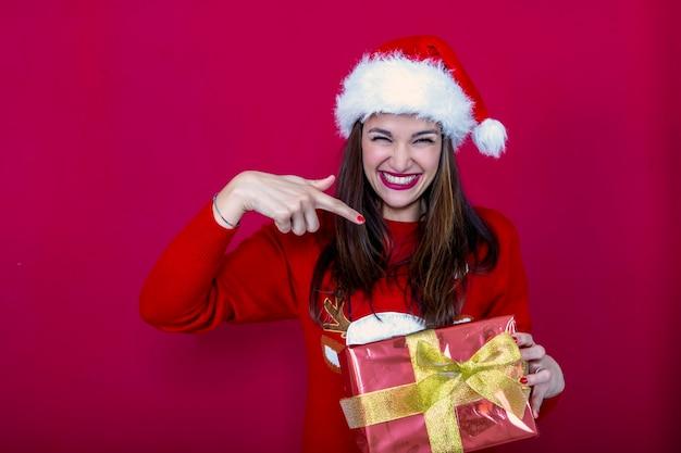 彼女の手でプレゼントを指しているサンタの帽子とクリスマスのトナカイのセーターの笑顔の女性