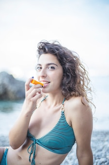 입술에 발삼을 적용하는 해변에 앉아 비키니 입은 웃는 여자