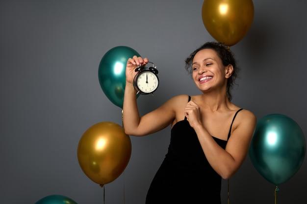 검은 드레스를 입고 웃고 있는 여성은 파티에서 기뻐하고 손에 든 알람 시계를 보고 자정입니다. 광고를 위한 복사 공간이 있는 회색 배경의 크리스마스, 새해, 생일 개념 축하