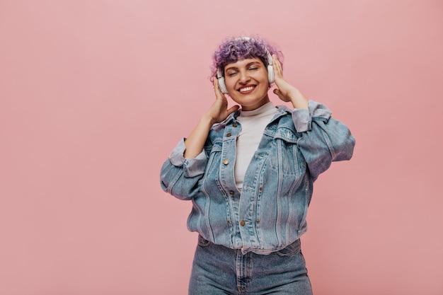 블루 데님 재킷에 웃는 여자는 눈을 감고 음악을 듣는다. 핑크에 포즈 흰색 헤드폰에 여자입니다.