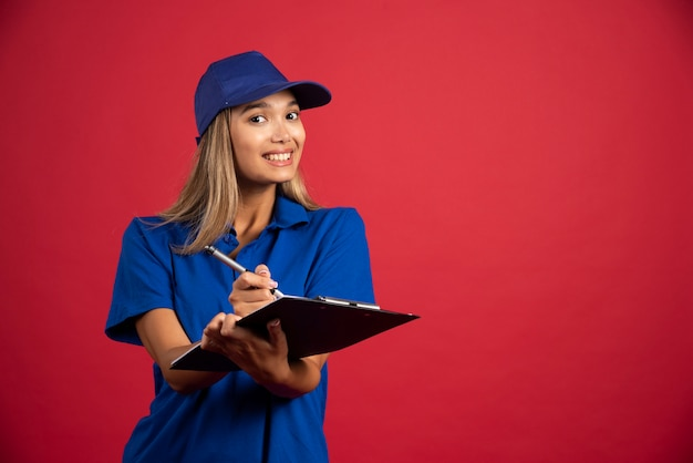 鉛筆でクリップボードに書く青い制服を着た笑顔の女性。