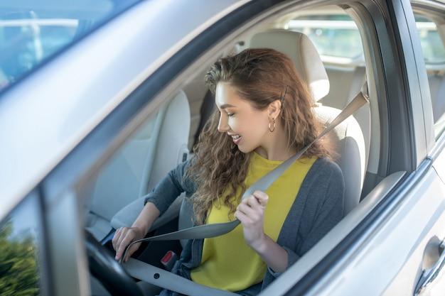 シートベルトを身に着けている車の中で笑顔の女性