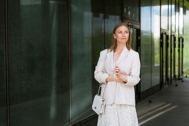 彼女のハンで携帯電話を持ってオフィスビジネスの女性のそばに立っているカジュアルな服を着た笑顔の女性...