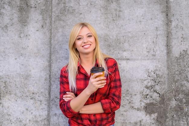 종이 머그잔을 들고 체크 무늬 빨간색 셔츠에 웃는 여자