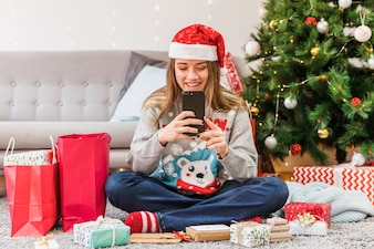 Smiling woman in Christmas hat messaging on floor