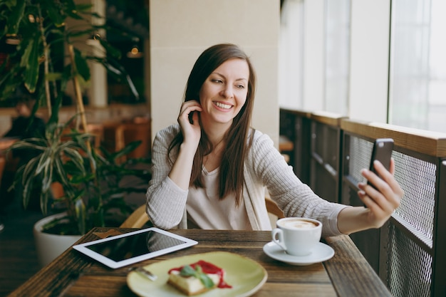 カプチーノ、ケーキ、携帯電話で自分撮りをしている、自由な時間の間にレストランでリラックスしてコーヒーショップで笑顔の女性。 pcタブレットコンピューターと一緒に座っている女性はカフェで休む。ライフスタイルのコンセプト