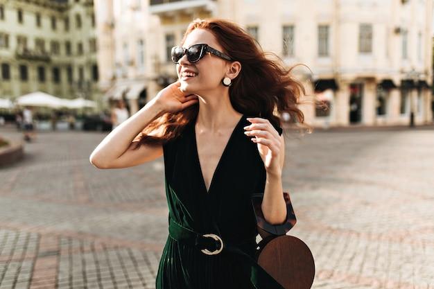 진한 녹색 옷을 입고 웃는 여자는 도시 산책을 즐긴다