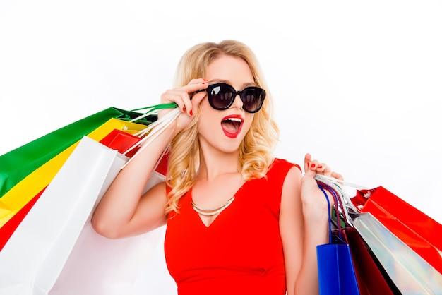 Улыбающаяся женщина в платье и очках, держащая пакеты с одеждой