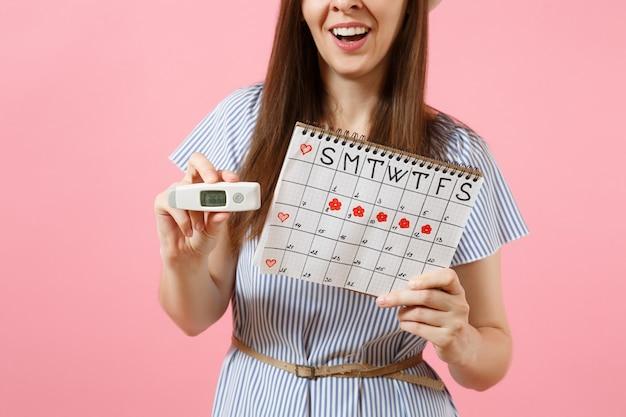 ドレスを着た笑顔の女性が手に温度計、ピンクの背景で隔離の月経日をチェックするための女性の期間カレンダーを保持します。医療ヘルスケア、排卵婦人科の概念。スペースをコピーします。