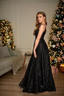 クリスマスツリーの上のイブニングドレスの笑顔の女性