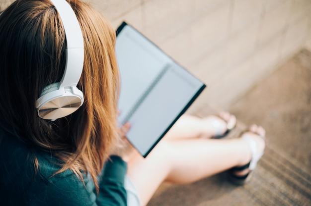Усмехаясь женщина в книге чтения eyeglasses и слушать к музыке с наушниками в парке внешнем против солнечного света, концепции образа жизни города.