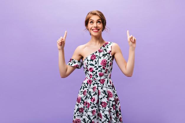 花の衣装を着た笑顔の女性は、テキストの場所を指しています。孤立した背景にポーズをとってモダンな明るい服を着たうれしそうなスタイリッシュな女の子。