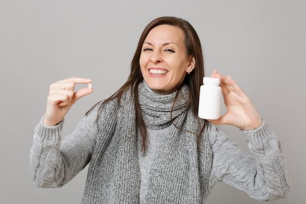 Улыбающаяся женщина в сером свитере, шарфе держит таблетки лекарства, таблетки аспирина в бутылке, изолированной на сером фоне. концепция холодного сезона лечения больных заболеваний здорового образа жизни. копируйте пространство для копирования.