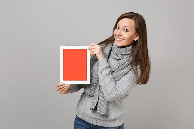 灰色のセーター、スカーフは灰色の背景で隔離の空白の空の画面でタブレットpcコンピューターを保持します。寒い季節のコンセプトをコンサルティングする健康的なライフスタイルのオンライン治療。コピースペースをモックアップします。