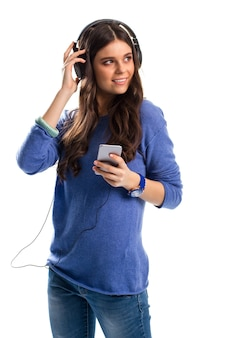 Улыбающаяся женщина в наушниках. дама в свитере с телефоном. гаджет с множеством функций. лучшие проводные наушники.