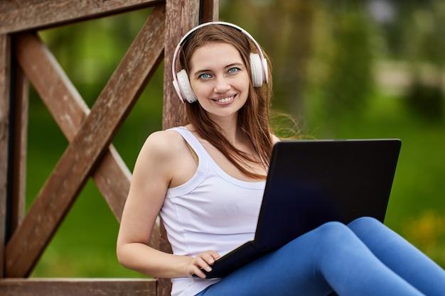 Улыбающаяся женщина в наушниках делает удаленную работу с ноутбуком на открытом воздухе