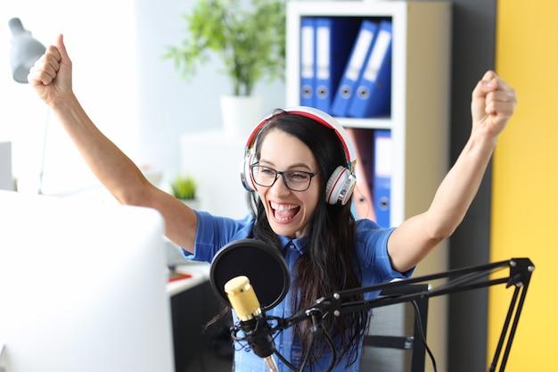 라디오 방송국 라디오 작업에서 마이크 앞에서 기뻐하는 헤드폰을 끼고 웃는 여자