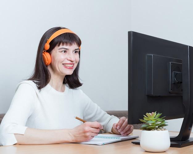 Улыбающаяся женщина в наушниках сидит за столом у себя дома, глядя на экран монитора, делая заметки