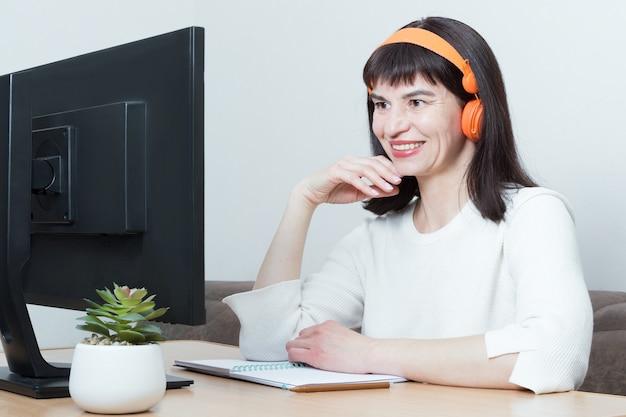 Улыбающаяся женщина в наушниках сидит за столом, глядя на экран монитора