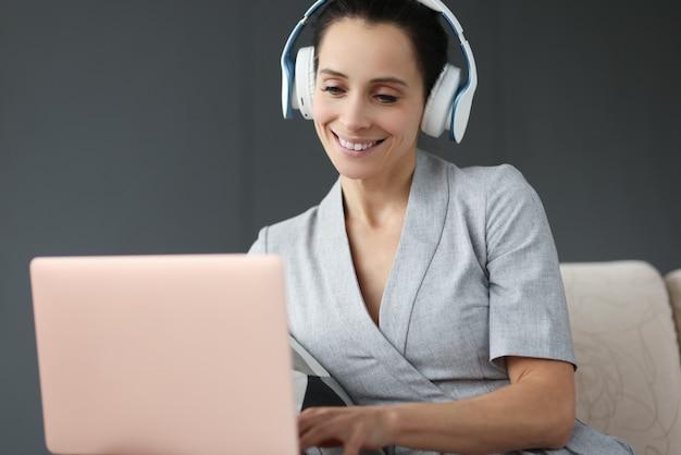 헤드폰에 웃는 여자는 노트북 뒤에 작동합니다. 원격 작업 개념