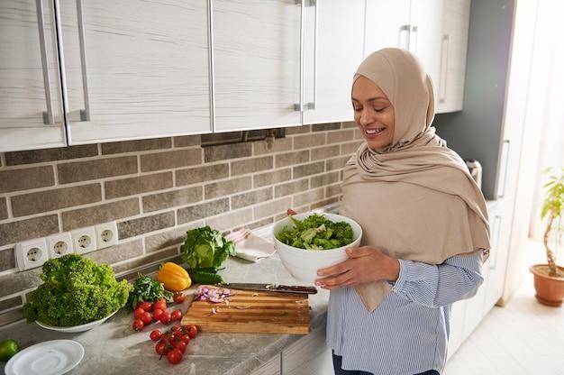 그녀의 국내 부엌에 서서 건강한 비건 샐러드로 가득 찬 하얀 그릇을 들고 히잡에 웃는 여자