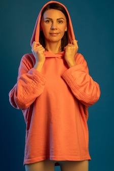 探しているフード付きスウェットシャツの笑顔の女性