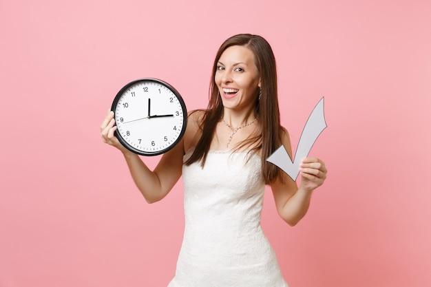 Улыбающаяся женщина в кружевном белом платье держит галочку и круглый будильник