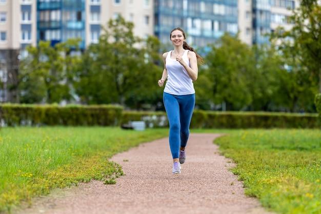 Улыбающаяся женщина в леггинсах бежит в городском саду утром