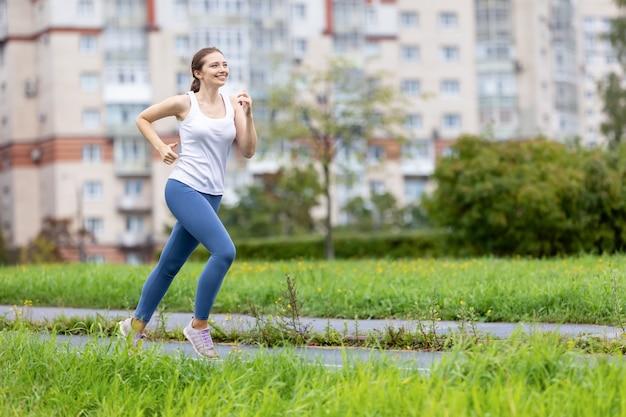Улыбающаяся женщина в леггинсах бежит в общественном парке утром
