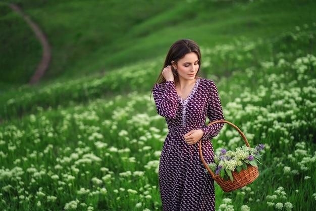 花が咲く牧草地でロング ドレスを着た笑顔の女性