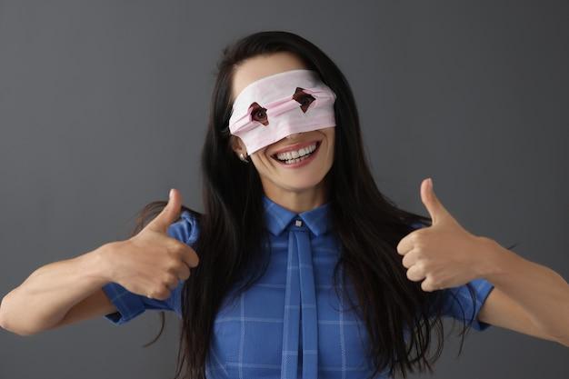 顔にマスクで笑顔の女性は、医療マスクの概念の強制着用を親指を保持します