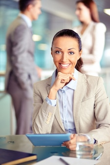 Smiling woman in office with tablet