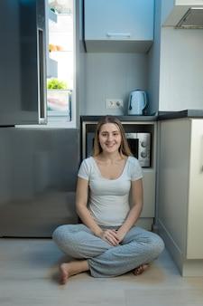 夕方に開いている冷蔵庫の隣のキッチンの床に座っているパジャマで笑顔の女性