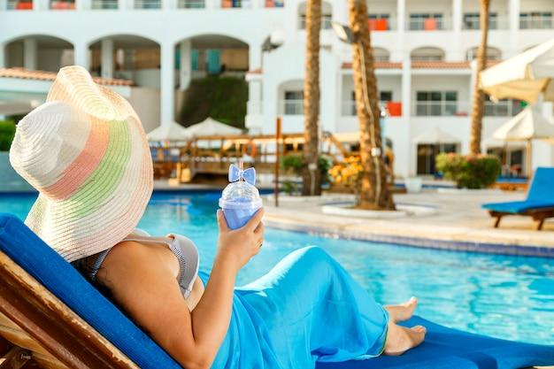 Улыбающаяся женщина в купальнике парео и шляпе у бассейна.