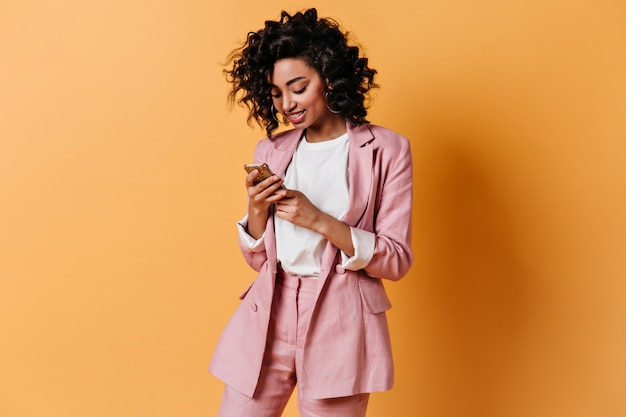 Улыбающаяся женщина в розовой куртке отправляет текстовое сообщение