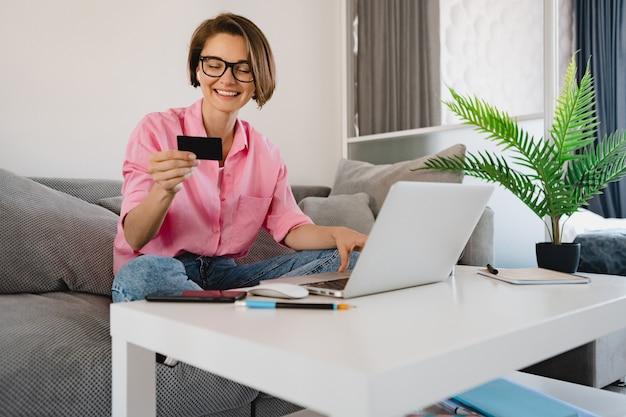 Улыбающаяся женщина в розовой рубашке сидит на диване у себя дома за столом, держа в руках кредитные машины, оплачивая покупки онлайн на ноутбуке из дома