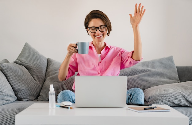 ラップトップの家でオンラインで作業しているテーブルで自宅のソファでリラックスしてお茶を飲んで座っているピンクのシャツを着た笑顔の女性