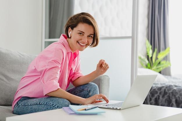 Улыбающаяся женщина в розовой рубашке расслабленно сидит на диване у себя дома за столом, работая онлайн на ноутбуке из дома